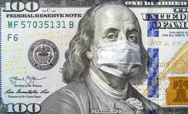 covid-19 coronavirus in den usa, 100-dollar-geldschein mit gesichtsmaske. coronavirus wirkt sich auf den globalen aktienmarkt aus. - pandemie stock-fotos und bilder