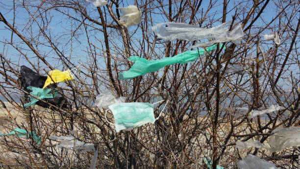Coronavirus (COVID-19) is contributing to pollution, as discarded face masks clutter urban parks & streets of the city along with plastic and other trash. Ecological pollution problem stock photo