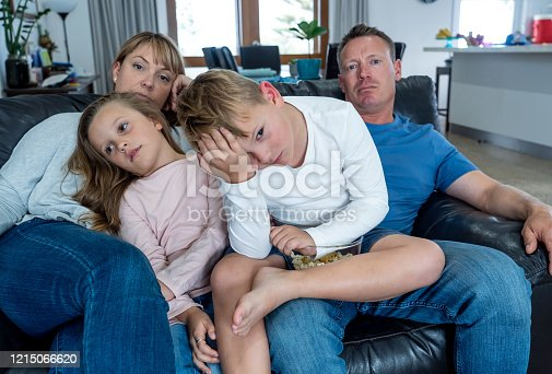 istock Coronavirus lockdow. Bored family watching tv helpless in isolation at home during quarantine COVID 19 Outbreak. Mandatory lockdowns and self isolation recommendations forces families stay home. 1215066620