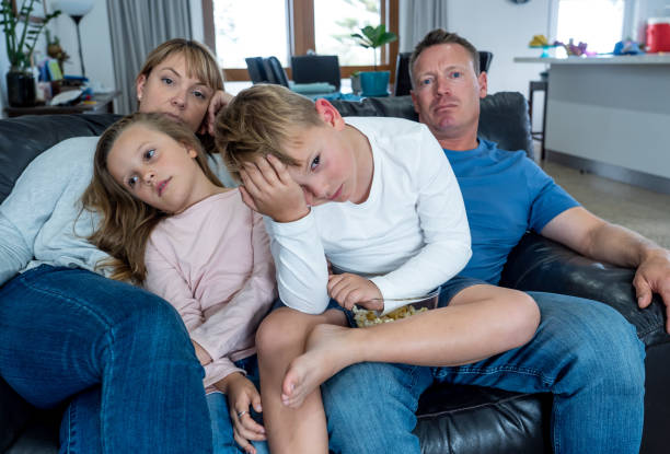 Coronavirus lockdow. Bored family watching tv helpless in isolation at home during quarantine COVID 19 Outbreak. Mandatory lockdowns and self isolation recommendations forces families stay home. Coronavirus lockdow. Bored family watching tv helpless in isolation at home during quarantine COVID 19 Outbreak. Mandatory lockdowns and self isolation recommendations forces families stay home. quarantine stock pictures, royalty-free photos & images