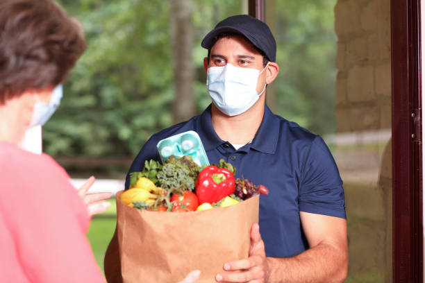 Coronavirus: Man delivers groceries to senior woman at home. stock photo
