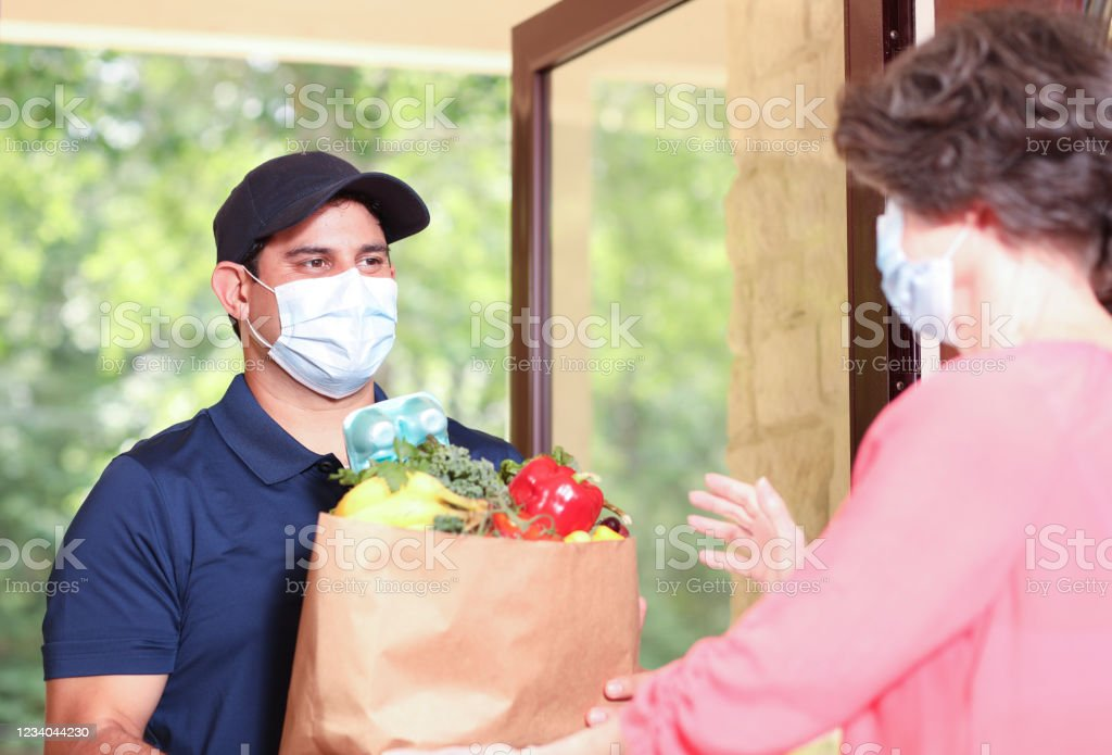 Coronavirus: Man delivers groceries to senior woman at home. Latin descent man delivers groceries to a senior adult woman at her home.  They both wear protective face masks during the delivery process.  Front door. A Helping Hand Stock Photo