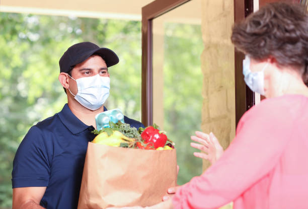 Coronavirus: Man delivers groceries to senior woman at home. Latin descent man delivers groceries to a senior adult woman at her home.  They both wear protective face masks during the delivery process.  Front door. covid stock pictures, royalty-free photos & images