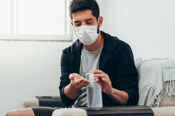 Coronavirus. Mann in Quarantäne trägt Schutzmaske, die seine Hände mit Alkoholgel entstatten – Foto