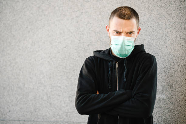 Coronavirus. Man wearing medical protective mask on a gray wall background. Prevent Covid-19, flu. Feeling bad in city. Person needs help. Virus, pandemic, panic concept.