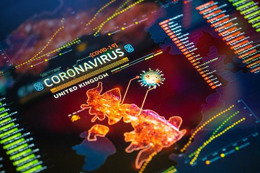 Coronavirus (COVID-19) Outbreak in United Kingdom Statistics close-up on digital display. Quarantine map.