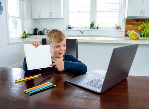 Coronavirus Ausbruch. Sperrung und Schulschließungen. Schuljunge mit Gesichtsmaske beobachtet Online-Bildungskurse gefühl und deprimiert zu Hause. COVID-19 Pandemie zwingt Kinder zum Online-Lernen. – Foto
