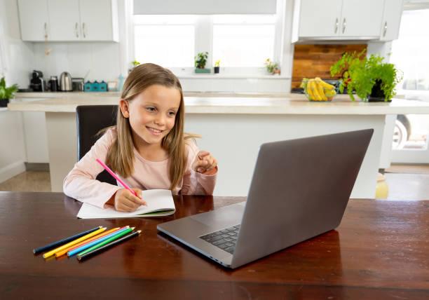 Coronavirus Ausbruch. Sperrung und Schulschließungen. Schulmädchen beobachten Online-Bildungskurs, glücklich im Gespräch mit Lehrer im Internet zu Hause. COVID-19 Pandemie zwingt Kinder zum Online-Lernen. – Foto