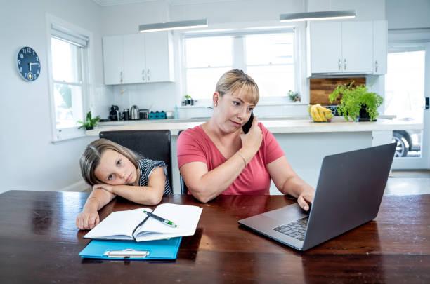 Coronavirus Outbreak Schulen und Büros schließen. Gestresste Mutter zu bewältigen mit Fernarbeit und gelangweilte Tochter. COVID-19-Abschaltungen und Quarantänen zwingen Eltern, von zu Hause aus zu arbeiten und zu Hause zu arbeiten. – Foto
