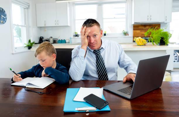 Coronavirus Outbreak Schulen und Büros schließen. Gestresste Eltern, die versuchen, mit Fernarbeit und Homeschooling fertig zu werden. COVID-19 Pandemie kräfte abschalten, Quarantäne, Online-Lernen und Arbeit von zu Hause aus. – Foto