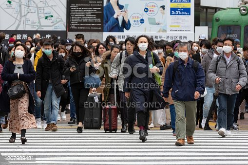 Tokyo, Japan, February 22, 2020 - Pedestrians wearing surgical mask to prevent infectious diseases walk in Shibuya's famous scramble crossing.