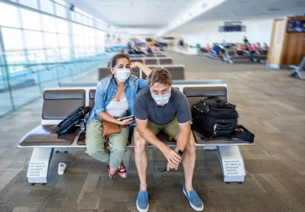Coronavirus-Ausbruch Reisebeschränkungen. Reisende mit Gesichtsmaske am internationalen Flughafen von Flugstornierung und Reiseverbot betroffen. COVID-19-Pandemie und Länderstillstände. – Foto
