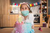 Charming preschool age girl celebrating her 5th birthday at home because of pandemic of COVID-19 in her country wearing mask for protection