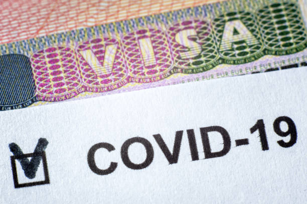 COVID-19 coronavirus pandemic and travel concept, document with COVID positive test and Visa stamp in passport. stock photo