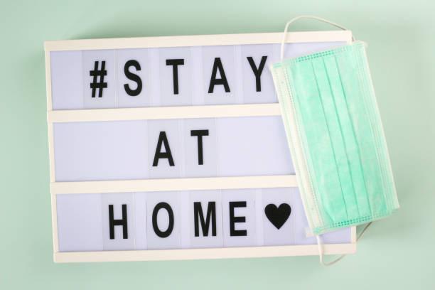 """coronavirus pandemic global message """"stay at home""""  on lightbox. covid-19 self-isolation, prevention and healthcare concept. - prevenzione delle malattie foto e immagini stock"""