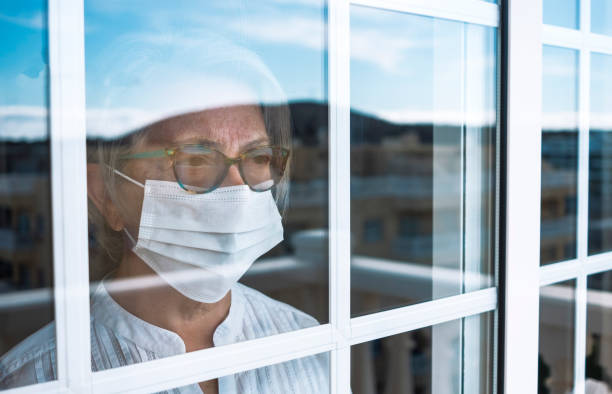 Coronavirus pandemic, senior woman in self quarantine to avoid contagion of infection by virus covid-19. Stays home looking outdoor from the window. Prevention concept Coronavirus pandemic, senior woman in self quarantine to avoid contagion of infection by virus covid-19. Stays home looking outdoor from the window. Prevention concept quarantine stock pictures, royalty-free photos & images