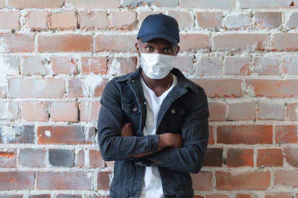 COVID, COVID-19, coronavirus, pandemic Young african black man wearing medical mask is standing in a cap with crossed arms shocked with coronavirus 2019 danger on background of ruined red brick wall stock photo