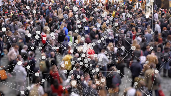 Visualization of coronavirus multiplying with a background of people at a train station concourse.
