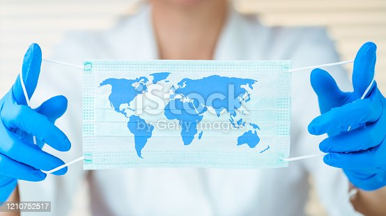 Laboratory worker holding protective mask with world map
