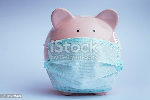 Piggy bank wearing medical mask. Coronavirus concept.
