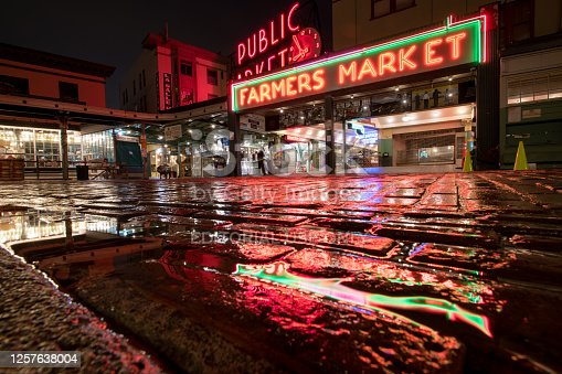 Seattle, USA - Apr 22, 2020: Deserted Pike Place Market illuminated with reflections in a puddle early in the night at the height of the Coronavirus Stay at home order.
