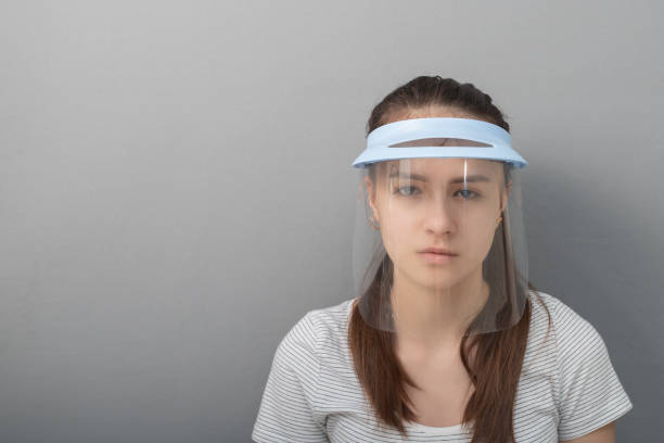 Coronavirus Prevention Young woman in a protective mask screen with a visor on a gray background stock photo