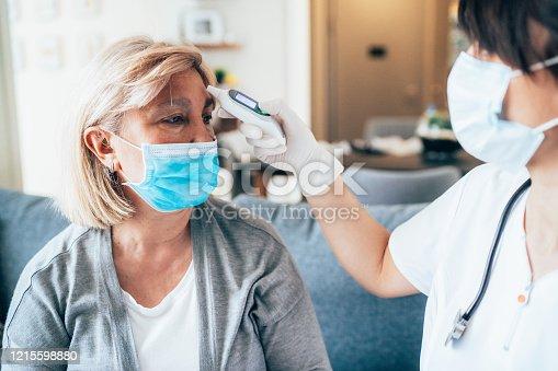 Female doctor measured temperature of the senior patient