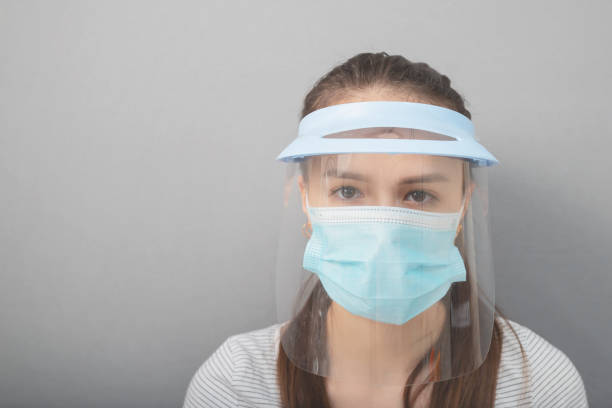 Coronavirus protection, health care and hygiene. Young woman in a protective mask screen with a visor on a gray background stock photo