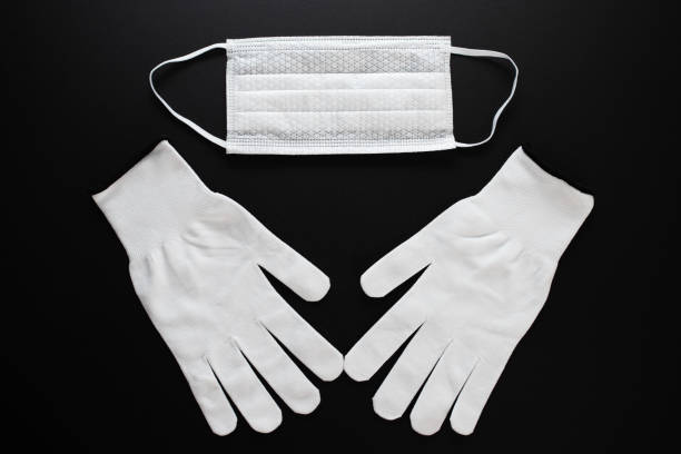 Coronavirus protection. White antibacterial medical mask and gloves on a black background stock photo