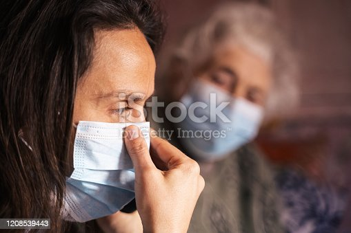 Young woman with her grandmother, discussing the coronavirus. Both with protective masks on their face.