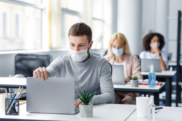 Coronavirus quarantine and office work with colleagues keeping social distancing. Portrait of young man in protective mask make video call with client stock photo