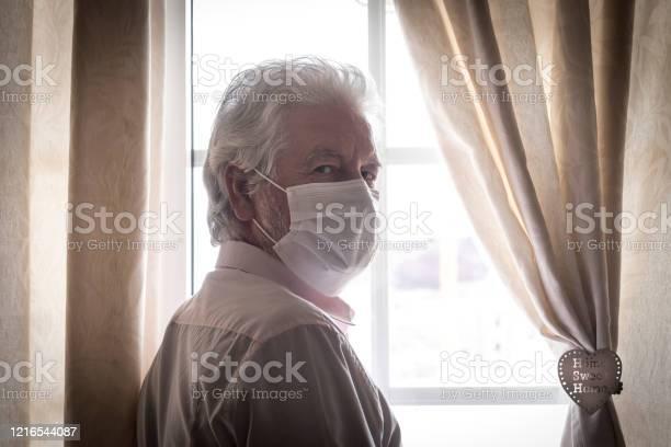 Coronavirus quarantine senior man wearing protective mask behind the picture id1216544087?b=1&k=6&m=1216544087&s=612x612&h=kmw c3ibwgysno8i7os0iai3smzsjjvec13plhvazfq=