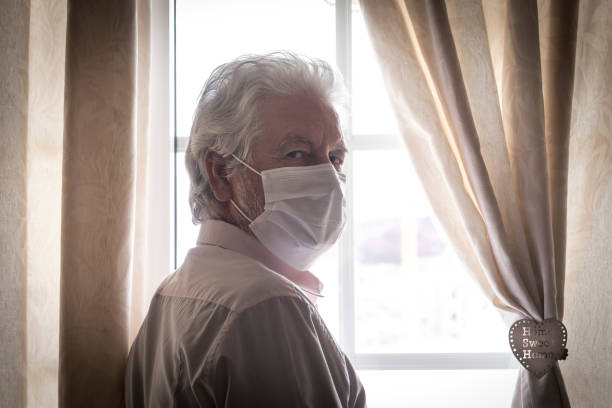 coronavirus quarantine. senior man wearing protective mask behind the window stay at home to avoid contagion by covid-19 - responsibility and prevention concept - old men window imagens e fotografias de stock