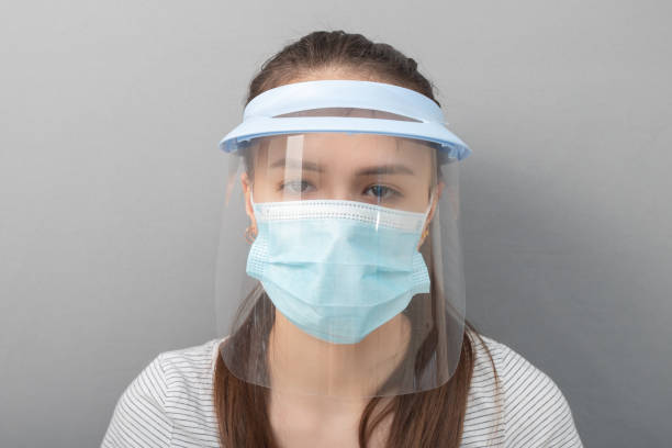 Coronavirus Remedy Young woman in a protective mask screen with a visor on a gray background stock photo
