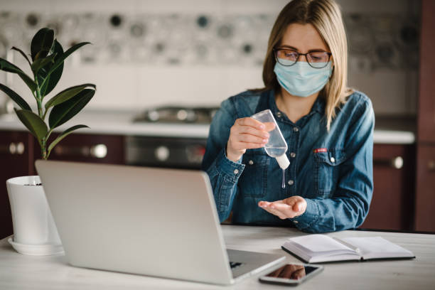 Coronavirus. Sanitizer gel. Business woman working, wearing protective mask in quarantine. Cleaning hands antibacterial gel to eliminate germs. Stay at home. Girl learns, using laptop. Freelance.
