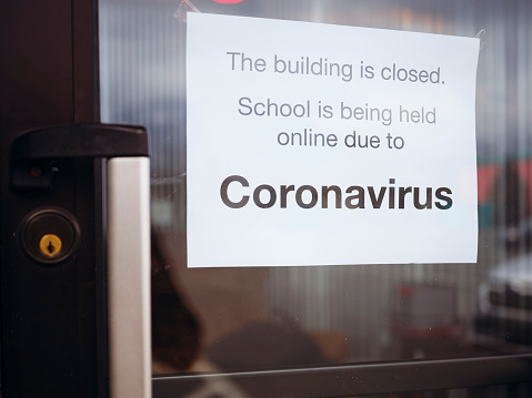 A door to a school with a sign stating that it is closed by the Coronavirus COVID-19 pandemic.