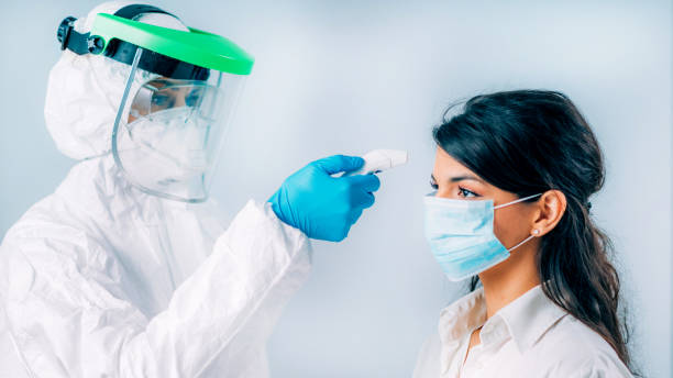 Coronavirus Screening. Medical worker in protective suit checking body temperature with contactless body thermometer, young woman wearing protective mask stock photo