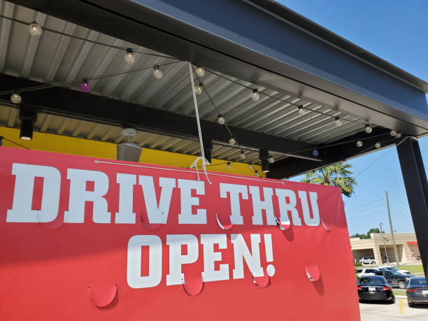 """Coronavirus sights. 'Drive Thru Open' sign outside restaurant. Coronavirus sights. A """"Drive Thru Open"""" banner sign outside a restaurant in USA. covid-19 stock pictures, royalty-free photos & images"""