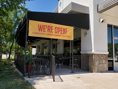 Coronavirus sights: 'We're open' sign at local restaurant in USA.