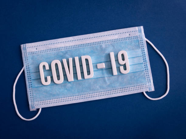 COVID-19 coronavirus sign lettering on a colored background with PPE mask stock photo
