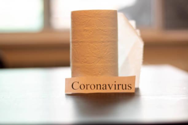 Coronavirus sign next to toilet paper. Theme of stocking up on essentials stock photo