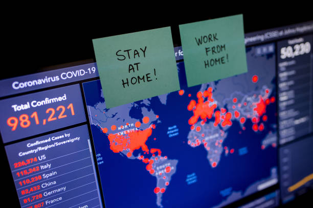 Coronavirus Statistics and World Map on Screen and Sticky Notes Reminding to Stay at Home stock photo