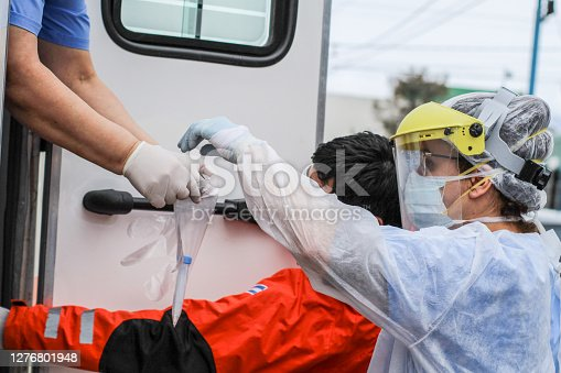 Female  doctor  handing  over  a coronavirus  test  of  a patient  to  the  nurse  to be  processed