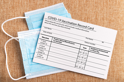 Coronavirus vaccination record card. Protective mask divided into two parts.Concept of defeating Covid-19. High quality photo