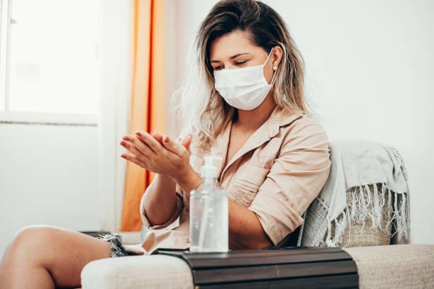 Coronavirus. Frau in Quarantäne trägt Schutzmaske desinitiieren ihre Hände mit Alkohol-Gel – Foto
