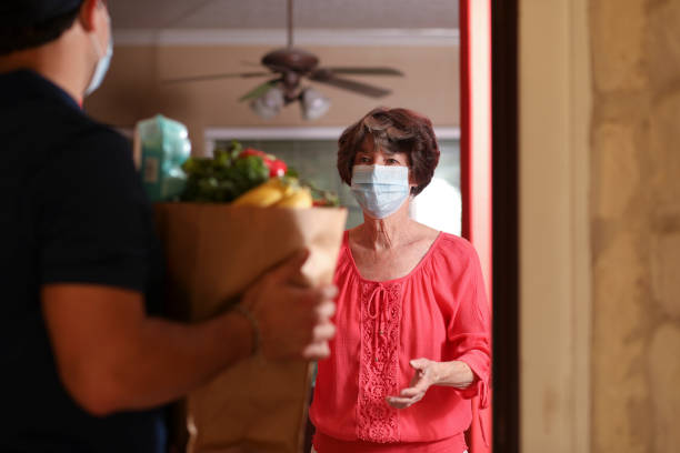Coronavirus: Woman receives groceries from delivery man at home. Senior adult woman receives groceries from delivery man at her home.  They both wear protective face masks during the delivery process.  Front door.  Focus on woman. Home interior background. covid stock pictures, royalty-free photos & images