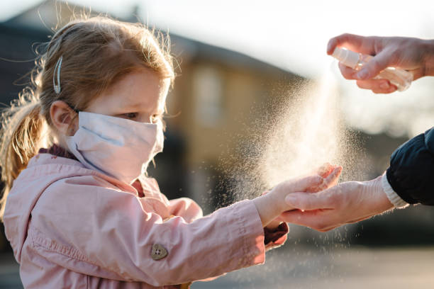 Coronavirus. Woman use spray sanitizer on hands child  in a protective mask on the street. Preventive measures against Covid-19 infection. Аntibacterial hand-washing spray. Illness protection.
