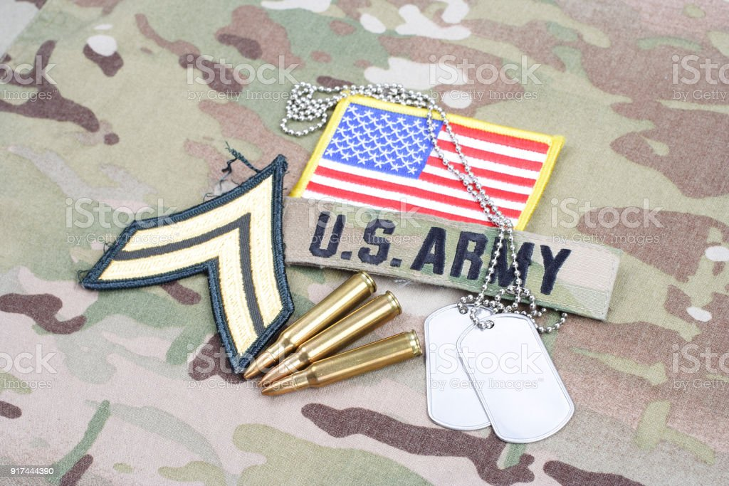 US ARMY Corporal rank patch, flag patch, with dog tag with 5.56 mm rounds on camouflage uniform stock photo