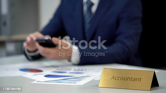 1130184417 istock photo Corporate accountant in business suit typing message on phone, papers on table 1130184190