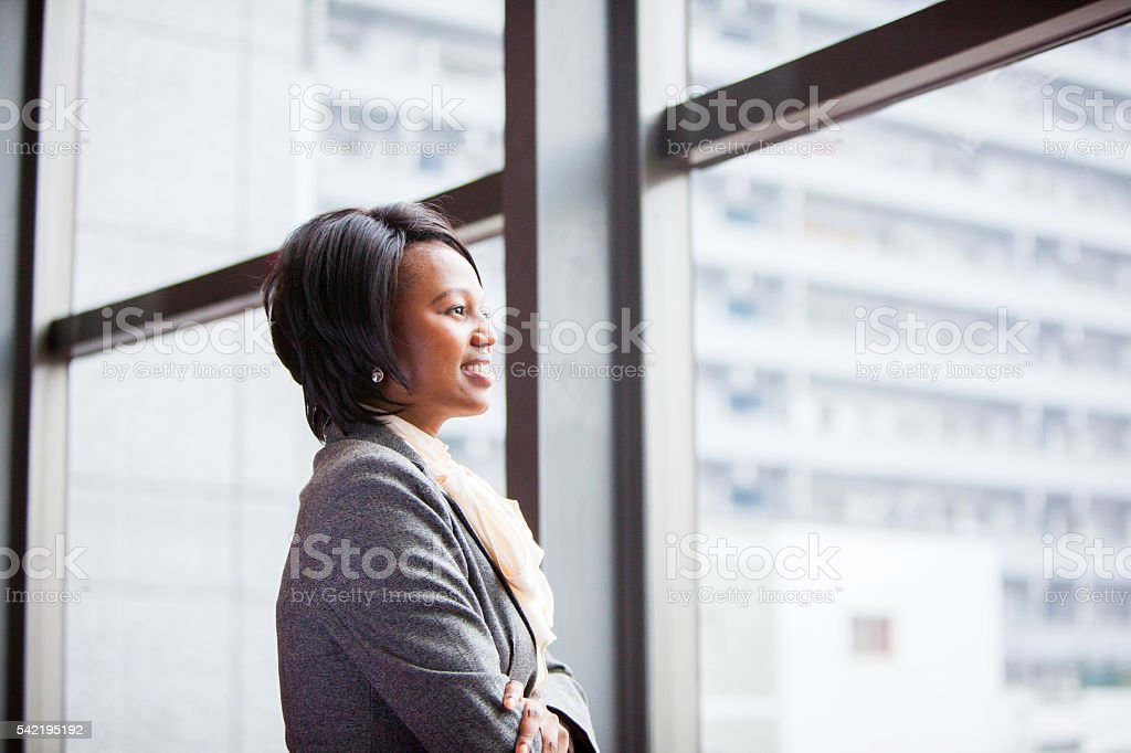 Corporate African female executive looking out the buidling window stock photo